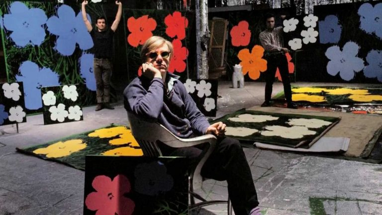 Andy Warhol: Flowers 1964 nella Factory con alle spalle serigrafie di Flowers